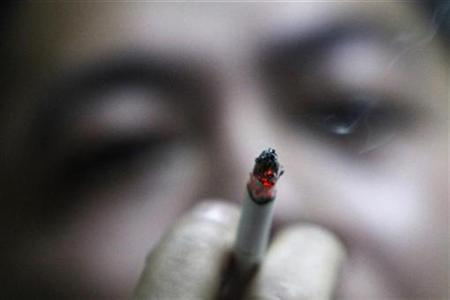 A man smokes at an office in Shanghai March 3, 2009. REUTERS/Aly Song