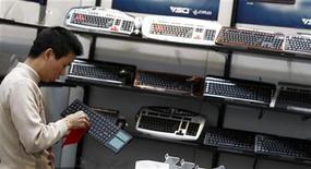 <p>Hanover, un uomo pulisce una tastiera ad uno stand REUTERS/Fabrizio Bensch</p>