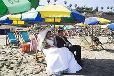 <p>Жених и невеста отдыхают на пляже в Лиме, 12 февраял 2010 года. Тайваньский отель устроил импровизированную свадьбу для пары из Словакии, застрявшей на острове на шесть дней из-за ограничившего транспортное сообщение в небе над Европой вулканического пепла. REUTERS/Enrique Castro-Mendivil</p>