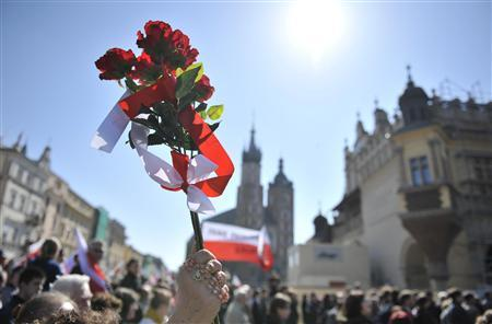 People wave flowers during the funeral procession for late Polish President Lech Kaczynski outside of Wawel Royal Castle in Krakow, April 18, 2010. REUTERS/Michal Zagumny