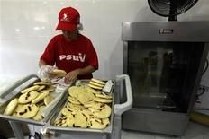 <p>A woman prepares arepas, a form of cornmeal flatbread usually filled with cheese or meat, at state-run Arepa Socialista (Socialist Arepa) restaurant in Caracas April 16, 2010. REUTERS/Jorge Silva</p>