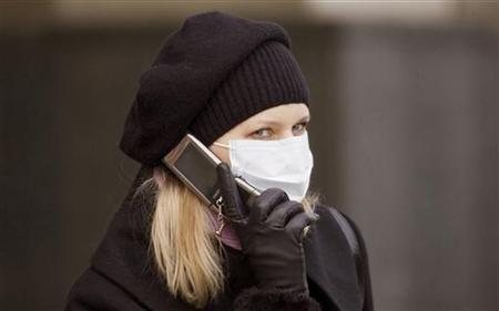 A woman wearing protective mask talks on the phone in Lviv, October 31, 2009. REUTERS/Vasily Fedosenko