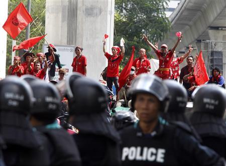 Anti-government ''red shirt'' protesters waves red flags as they stand on top of a barricade built with bamboo poles and tyres facing riot police at an intersection close to the Silom Road financial district in Bangkok April 21, 2010. REUTERS/Eric Gaillard