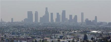 The skyline of downtown Los Angeles through a layer of smog is seen in the distance from a rooftop in Hollywood, California, May 31, 2006. REUTERS/Fred Prouser