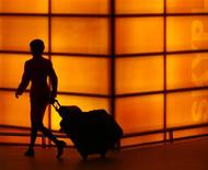 <p>A woman is silhouetted as she walks with her baggage at Hong Kong International Airport April 29, 2008. REUTERS/Victor Fraile</p>