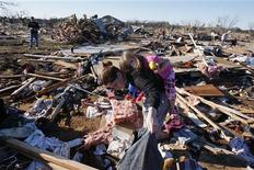 <p>Una donna con la sua bambina cerca tra i resti della casa distrutta dal passaggio di un tornado, in Oklahoma. REUTERS/Jessica Rinaldi</p>