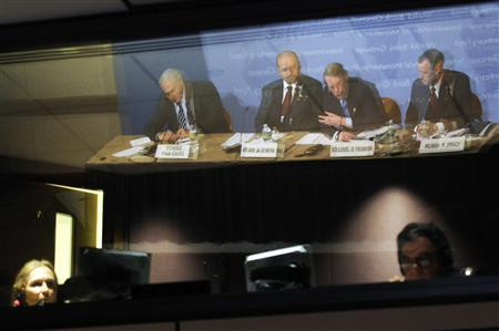 Technicians are visible in the production booth as IMF Managing Director Dominique Strauss-Kahn (From L, reflected in glass), Finance Minister of Bahrain Ahmad bin Mohammed Al Khalifa and World Bank President Robert Zoellick hold a news conference after the meeting of the Development Committee at the International Monetary Fund/World Bank Spring Meetings at IMF headquarters in Washington, April 25, 2010. The unidentified man at right is an IMF/World Bank moderator. REUTERS/Jonathan Ernst