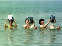 """<p>Японские туристки читают журналы в Мертвом море 14 сентября 1999 года. Китайская пловчиха Чжан Цзи учится есть и спать """"на плаву"""", чтобы принять участие в 40-часовом марафоне в открытой воде в августе. REUTERS/Ali Jarekji</p>"""