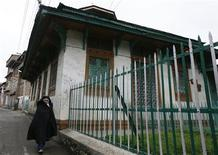 <p>A Kashmiri Muslim woman walks past the Rozabal Shrine in Srinagar April 22, 2010. REUTERS/Danish Ismail</p>