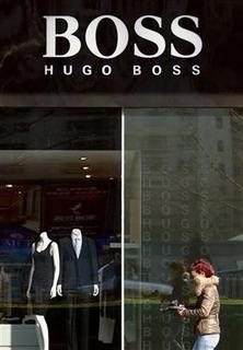 A shopper walks past a Hugo Boss store in central Beijing March 17, 2010. REUTERS/David Gray