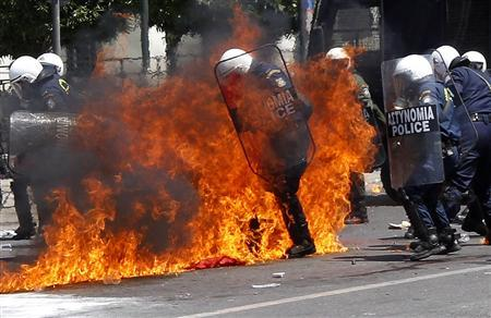 Policemen try to escape a fire from a petrol bomb during riots at a May Day rally in Athens May 1, 2010. REUTERS/Yiorgos Karahalis