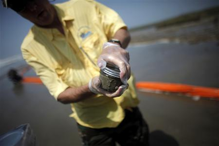 Andrew Nyman, Associate Professor Wetland Wildlife Management & Ecology of LSU AgCenter, collects samples of beach sand beside oil booms at the coast of South Pass, south of Venice, Louisiana, as oil leaking from the Deepwater Horizon wellhead continues to spread in the Gulf of Mexico, May 2, 2010. REUTERS/Carlos Barria