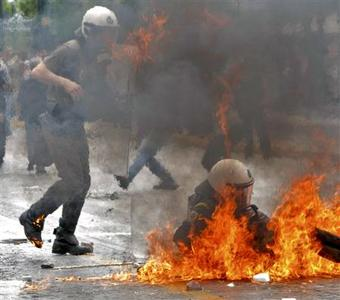 A riot policeman falls after being ihit with molotov cocktail near the Greek parliament in Athens during a nationwide strike in Greece, May 5, 2010. REUTERS/John Kolesidis