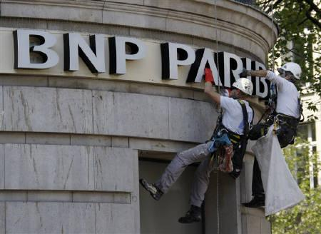 Workers, suspended in harnesses, clean the BNP Paribas bank sign on the headquarters facade near where pigeons roost in Paris April 21, 2009. REUTERS/John Schults/Files