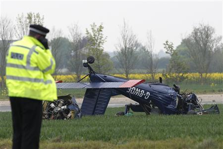 A police officer stands near a light aircraft that crashed with MEP for the UK Independence Party (UKIP) Nigel Farage on board at Hinton in the Hedges Airfield in Steane, May 6, 2010. REUTERS/Darren Staples