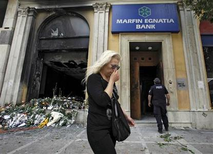 A woman passes a burned-out bank, May 6, 2010, which was set on fire during violent demonstrations in Athens yesterday. REUTERS/Pascal Rossignol