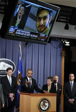 U.S. Attorney General Eric Holder (2nd L) and other top-ranking U.S. security officials face a news conference as suspect Faisal Shahzad (R) is pictured on a television screen at the Justice Department in Washington May 4, 2010. REUTERS/Kevin Lamarque