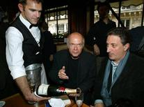 <p>Famous French Goncourt and Renaudot literary prize winners Pascal Quignard (L) and Gerard de Cortanze (R) are served champagne by a waiter as they celebrate in a Paris cafe, October 28, 2002. REUTERS/Jack Dabaghian</p>
