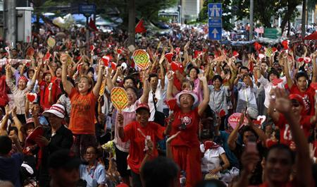 Thousands of anti-government ''red shirt'' protesters cheer as their leaders make an announcement at their encampment in Bangkok's main shopping district May 10, 2010. REUTERS/Jerry Lampen