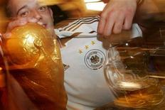<p>A German soccer fan displays a replica World Cup at a traditional beer hall in Munich, June 18, 2006. REUTERS/Toby Melville</p>