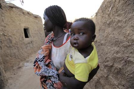 A Sudanese woman carries her child in their home outside Sudan's capital Khartoum April 17, 2010. REUTERS/Mohamed Nureldin