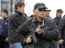 <p>Телохранитель расчищает путь для свергнутого президента Киргизии Курманбека Бакиева во время митинга в городе Ош 15 апреля 2010 года. Сторонники свергнутого президента Киргизии Курманбека Бакиева захватили здание администрации Джалалабадской области на юге страны и взяли в заложники губернатора, сообщили очевидцы с места событий. REUTERS/Denis Sinyakov</p>