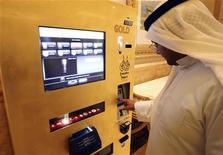 <p>Мужчина покупает золото в торговом автомате в Абу-Даби 13 мая 2010 года. В отеле Emirates Palace в Абу-Даби был запущен первый в мире торговый автомат, продающий золото. REUTERS/Mosab Omar</p>
