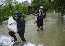 <p>Жители строят дамбу из мешков с песком в венгерском городе Мисколц 16 мая 2010 года. Как минимум четыре человека стали жертвами наводнений, начавшихся в Центральной Европе из-за проливных дождей. Тысячи людей эвакуированы, многие районы остались без энергоснабжения, а синоптики прогнозируют новые осадки. REUTERS/Arpad Kuruc</p>