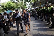 """<p>Представители протестующих """"красных рубашек"""" идут под кардон полиции в полицейский участок в Бангкоке, 20 мая 2010 года. Власти Таиланда добились порядка в столице страны после пожаров и ночных столкновений с оппозиционерами, не желавшими отдавать свой укрепленный лагерь в центре Бангкока. REUTERS/Damir Sagolj</p>"""