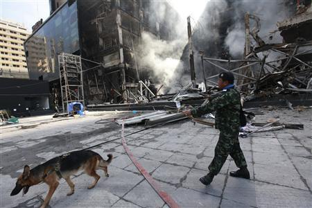 A Thai soldier patrols with a bomb sniffing dog at the Central World shopping mall building that was set on fire by anti-government ''red shirt'' protesters in Bangkok May 20, 2010. REUTERS/Kerek Wongsa