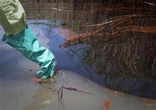 <p>Ecologistas toman muestras del agua contaminada por un derrame de petróleo, cerca del Paso Loutre, en Lusiana. Mayo 20 2010. Enojo, escepticismo y acusaciones de adulterar información cubrían el viernes a la petrolera BP Plc, mientras se debatía para contener un derrame de crudo de un pozo submarino, que desde hace un mes vierte una marea negra sobre el Golfo de México. REUTERS/Lee Celano</p>