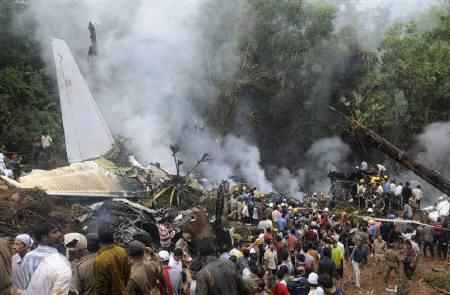 Onlookers and firefighters stand at the site of a crashed Air India Express passenger plane in Mangalore May 22, 2010. REUTERS/Stringer
