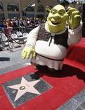 """<p>Человек, переодетый в костюм Шрэка, стоит рядом со звездой на """"Аллее славы"""" в Голливуде, 20 мая 2010 года. Шрэк уже не так радует зрителей по всему миру - четвертая часть мультсериала про большого зеленого огра от студии DreamWorks Animation SKG Inc заняла первое место по сборам в США за минувшие выходные, но не оправдала прогнозов специалистов. REUTERS/Fred Prouser</p>"""