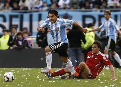 Argentina's Carlos Tevez (L) runs for the ball as Daniel Imhof of Canada looks on during their friendly soccer match in Buenos Aires, May 24, 2010. REUTERS/Santiago Pandolfi