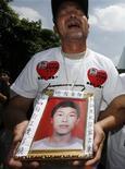 <p>Ma Zishan piange portando la foto del figlio Ma Xiangqian in foto d'archivio. REUTERS/Bobby Yip</p>