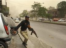 """<p>Пакистанский полицейский спешит к месту перестрелки у мечети в городе Лахор 28 мая 2010 года. Вооруженные люди атаковали мечети в двух районах города Лахор на северо- востоке Пакистана, захватив заложников и убив по меньшей мере 53 человек, сообщили источники в правительстве страны, полиции и службы """"скорой помощи"""". REUTERS/Mani Rana</p>"""