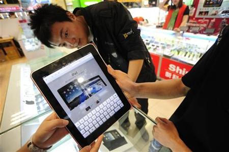 A shop assistant (L) displays an iPad at an electronic products store in Hefei, Anhui province May 28, 2010. Apple has yet to announce a launch date for mainland China, which could prove a much more difficult market to profit from. The iPad sells for about 4998 yuan (about $731). REUTERS/Stringer