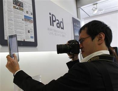 A man takes a photo of an iPad at an Apple store in Tokyo May 28, 2010. REUTERS/Kim Kyung-Hoon