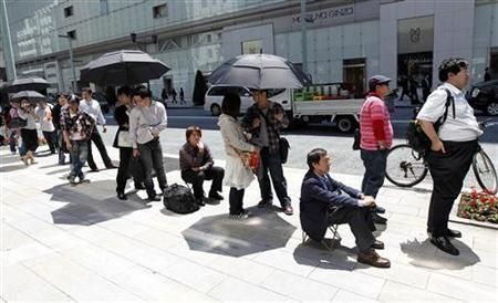 People stand in a line to purchase Apple's iPad at an Apple store in Tokyo, May 28, 2010. REUTERS/Kim Kyung-Hoon