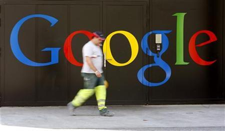 A construction worker walks past a logo next to the main entrance of the Google building in Zurich May 25, 2010. REUTERS/Arnd Wiegmann