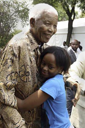 Former South African President Nelson Mandela hugs his great granddaughter Zenani Mandela in Diepkloof, Soweto in this December 7, 2008 handout picture. Zenani Mandela, 13, was killed in a car crash on June 11, 2010 after leaving a concert ahead of the World Cup kick off, the Nelson Mandela Foundation said. REUTERS/Nelson Mandela Foundation/Handout