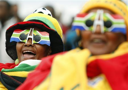 Spectators react during a public screening of the opening match of the 2010 World Cup in Motherwell township outside Port Elizabeth June 11, 2010. REUTERS/Howard Burditt