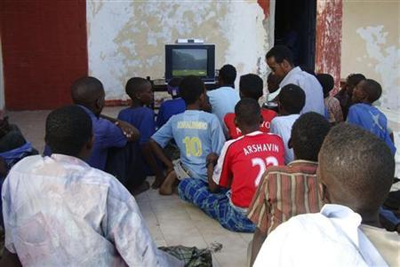People sit around a television set to watch the opening game of the 2010 World Cup in Mogadishu June 11, 2010. REUTERS/Feisal Omar