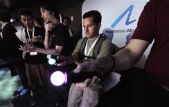 <p>Pessoas experimentam o PlayStation Move. A Sony irá lançar seu sistema de videogame com sensor de movimento em 15 de setembro, marcando sua entrada na maior tendência do mercado de games dois meses antes de sua concorrente Microsoft.15/06/2010.REUTERS/Phil McCarten</p>