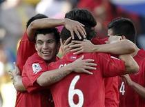 <p>Gary Medel (esq) comemora com seus colegas de equipe vitória da seleção chilena contra Honduras, no estádio Mbombela. Após 48 anos sem conseguir vencer na Copa do Mundo, os chilenos estão aliviados pelo resultado positivo contra Honduras, mas também estão preocupados com a incapacidade do próprio time de decidir a partida. 16/06/2010 REUTERS/Adnan Abidi</p>