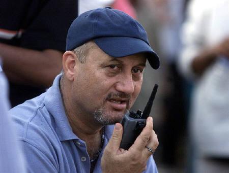 Bollywood actor Anupam Kher talks on a walkie-talkie while directing his Hindi film 'Om Jai Jagdish' in Mumbai, April 15, 2002. REUTERS/Arko Datta/Files