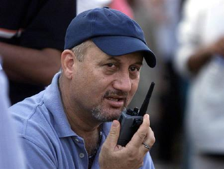 Bollywood actor Anupam Kher talks on a walkie-talkie while directing his Hindi film 'Om Jai Jagdish' in Mumbai, April 15, 2002. REUTERS/Arko Datta/Files