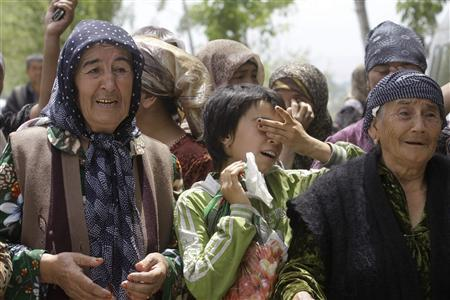 Ethnic Uzbek refugees cry while waiting for permission to move to Uzbekistan at the border line between Kyrgyzstan and Uzbekistan near the city of Osh, June 16, 2010. REUTERS/Stringer