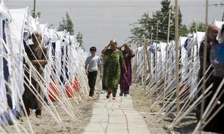 Ethnic Uzbeks walk between tents at a refugee camp in the village of Yorkishlak on the Kyrgyz-Uzbek border, some 400 km (249 miles) east of Tashkent, June 18, 2010. REUTERS/Shamil Zhumatov