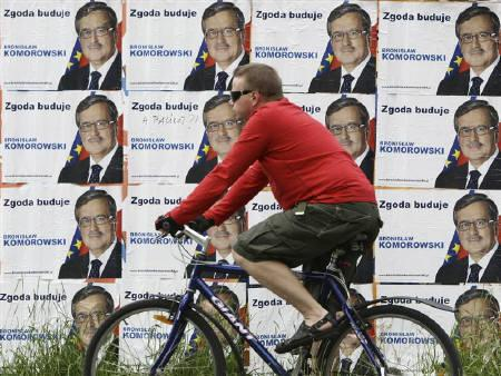 A cyclist passes posters of Civic Platform (PO) presidential candidate Bronislaw Komorowski in centre of Warsaw June 19, 2010. REUTERS/Kacper Pempel